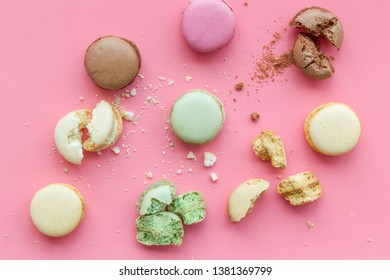 Brignt macarons for sweet break on pink background top view pattern