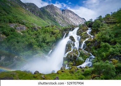 Briksdalsbreen waterfall long exposure photo. Briksdal, Norway national park and popular hiking path to glacier viewpoint.