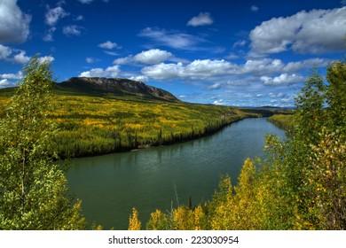 Brilliant autumn colors line the powerful Liard River in northern British Columbia, Canada
