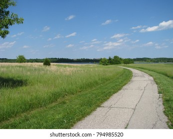 Brilliant blue sky with white clouds above a green landscape along the bicycle trail at Longview Lake park in Missouri.