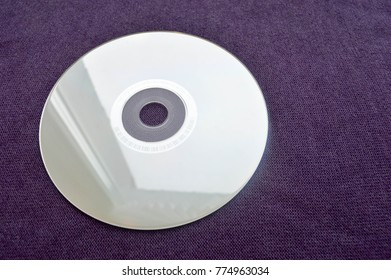 Brilliant compact disc. CD, DVD, Bluray disc on a violet background.