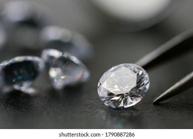 brilliant cut diamond held by tweezers on black background