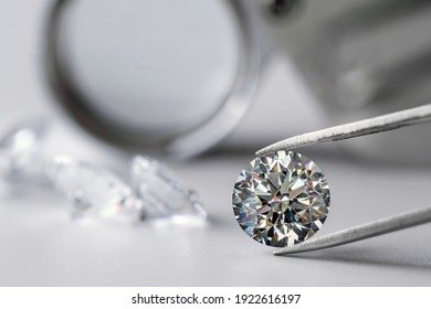 brilliant cut diamond held by tweezers on white background
