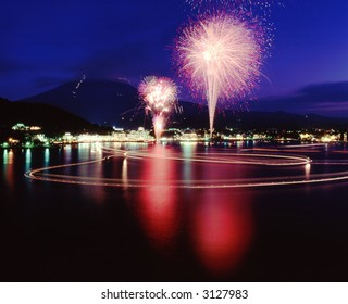 A brilliant display of Fireworks and their reflections in the water with Mount Fuji in the background