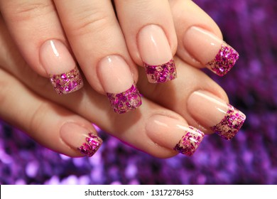Brilliant French manicure with lilac and golden small glitters on a purple background close-up. File art.
