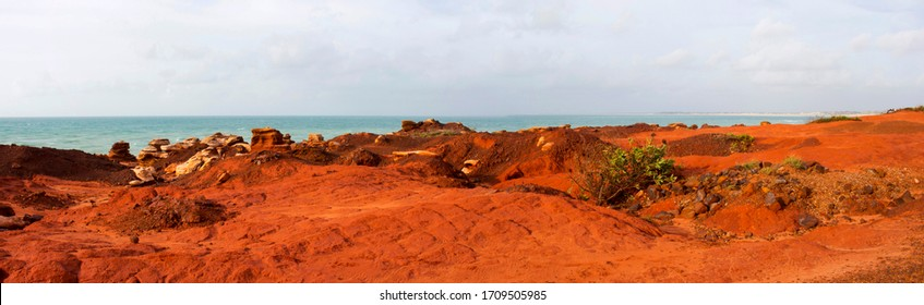 Brilliant orange ochre tones of stunning Gantheaume Point, a red-sandstone headland that juts out into the Indian Ocean from beautiful Cable Beach, Broome, Western Australia on a late hazy afternoon .