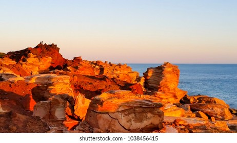 Brilliant orange red  tones of stunning Gantheaume Point, a red-sandstone headland that juts out into the Indian Ocean from beautiful Cable Beach, Broome, Western Australia on a late hazy afternoon