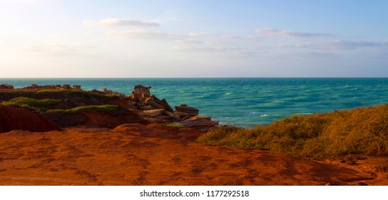 Brilliant orange red  tones of stunning Gantheaume Point, a red-sandstone headland that juts out into the Indian Ocean from beautiful Cable Beach, Broome, Western Australia on a late hazy afternoon.