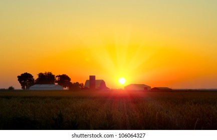 Brilliant orange sunrise over a Corn field in Iowa, and barn with a bright yellow sun on a cool fall morning.