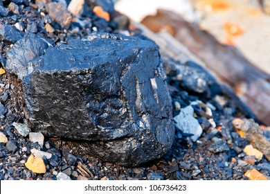 A brilliant piece of coal lying on the rock embankment.