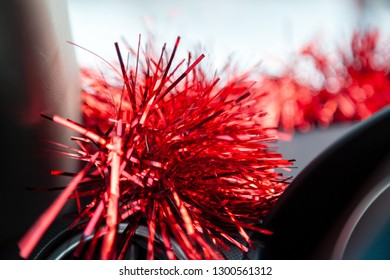 Brilliant red tinsel inside the car decorates the dashboard above the steering wheel flickering and uplifting the driver's excitement distracts from the gray everyday and brings the Christmas closer.