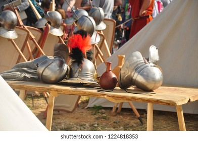 Brilliant Roman helmets piled on the table and hanging on the fence