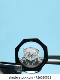 Brilliant round diamonds ring is being looked through a 10x loupe 3/4 top view with negative space on blue background