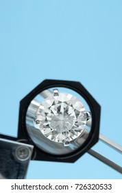 Brilliant round diamonds ring is being looked through a 10x loupe top on blue background with negative space