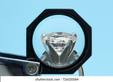 Brilliant round diamonds ring is being looked through a 10x loupe side view on blue background