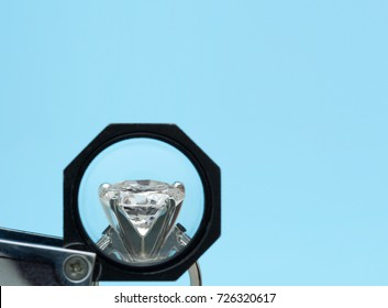 Brilliant round diamonds ring is being looked through a 10x loupe side view with negative space on blue background