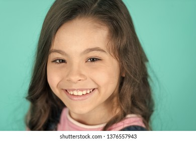 Brilliant smile. Kid happy carefree enjoy childhood. Child charming brilliant smile turquoise background. Kid girl long curly hair cheerful happy. Girl curly hairstyle adorable smiling face.