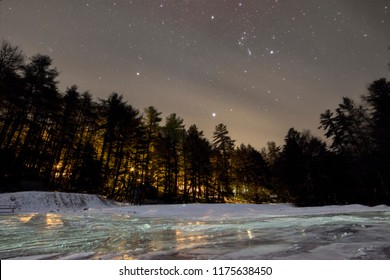 The brilliant stars of Orion shine through wisps of cloud.  Their light reflects off the icy frozen lake.  A warm glow from cabins in the woods lights the horizon.  New Germany State Park, Maryland.