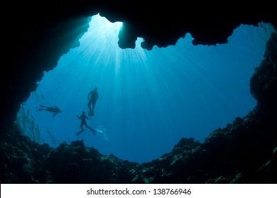 Brilliant sunbeams silhouette snorkelers at the top of a submerged sinkhole in Palau, Micronesia.  Palau is known for its high marine diversity and wonderful diving.