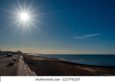 Brilliant sunlight with lens flare over a silhouetted beach and promenade at Brighton and Hove