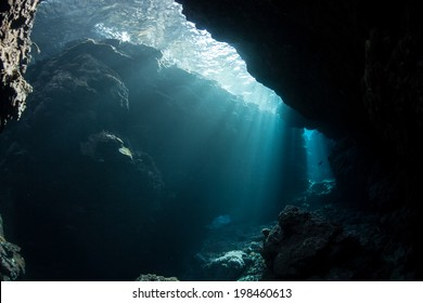 Brilliant sunlight penetrates a narrow crevice along the edge of a remote island in the Solomon Islands. This region is within the Coral Triangle and is known for its high marine habitat diversity.