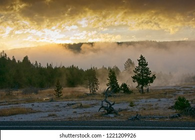 A brilliant sunrise above a thermal area in Yellowstone National Park on a cold morning