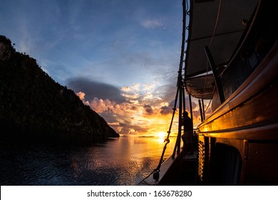 A brilliant sunset lights up the sky, the sea, and an Indonesian Pinisi schooner used as a diving live aboard in Raja Ampat, Indonesia. This region harbors fantastic scuba diving and high diversity.