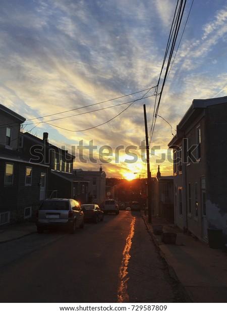 A brilliant sunset streaks across a cloudy sky in Manayunk, a Northwestern suburb of Philadelphia