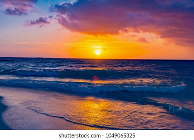 Brilliant vacation destination beach sunrise with colorful sand bright sea foam pink clouds