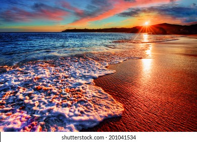 Brilliant vacation destination beach sunrise with colorful sand bright sea foam pink clouds and distant cliffs