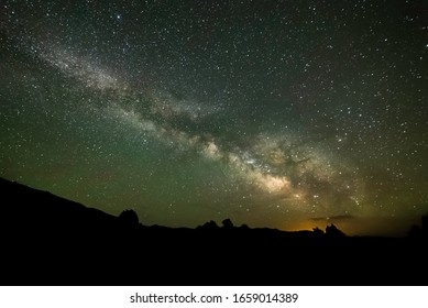 A brilliant view of the stars of the Milky Way Galaxy seen from Dark Night Skies North of Tonopah, Nevada, USA with the glow of Las Vegas on the horizon some 300 miles south.