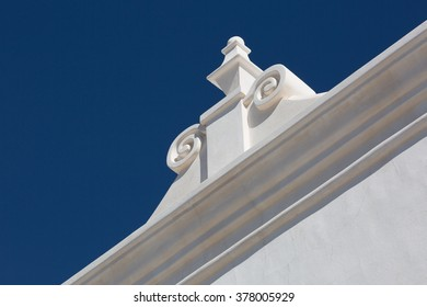 brilliant white classical roof ornament contrasts against deep blue sky