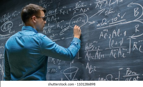 Brilliant Young Mathematician Approaches Big Blackboard and Finishes writing Sophisticated Mathematical Formula/ Equation.