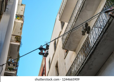 Brindisi, Italy - September 20 2018: Pairs of shoes are strung across apartment complexes in the urban center of the port city of Brindisi, Italy in the Puglia region