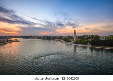 Brindisi, Italy - September 20 2018: The Italian Sailor Monument, promenade and bay as the sun sets and lights come on in the seaside port city of Brindisi Italy in the Southern region of Puglia.
