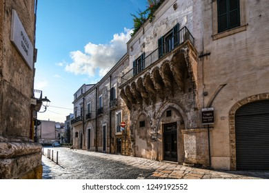 Brindisi, Italy - September 23 2018: A medieval street in the Old Town section features the Balsamo Loggia, a 14th century intricately carved balcony, in Brindisi, Italy located near Piazza Duomo.