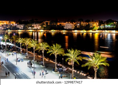 Brindisi, Italy - September 24 2018: Tourists and locals enjoy a late night on the boardwalk promenade at the port of Brindisi in the Puglia region of Southern Italy.