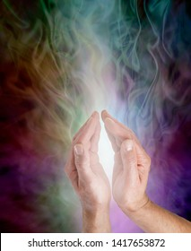 Bringing light into the darkness - male hands cupped around gentle white light rising up against an ethereal gaseous multicoloured background with copy space