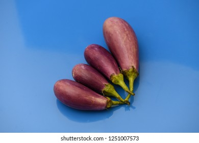 brinjal aubergines isolated on blue background closeup healthy vegetables diet violet organic food