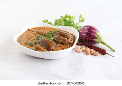 Brinjal or eggplant curry, which is an Indian vegetarian side dish for food like rice roti and chapati, in a ceramic bowl.