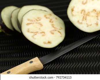 Brinjal, eggplant cut in slices on a black background