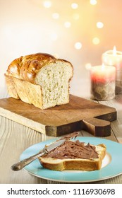 Brioche bread slice smeared with chocolate cream, in winter holidays mood with and candle light.