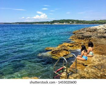 Brioni Beach, Pula, Croatia - July 4th, 2019: A mother and daughter relax with their feet in the ocean along the beautiful rocky Brioni Beach outside of Pula, Croatia along the Adriatic Sea.