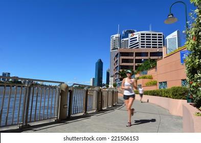 BRISBANE, AUS - SEP 26 2014:Runner runs on Brisbane riverside walk.It's a popular network of riverwalk pavements along the banks of the Brisbane River.