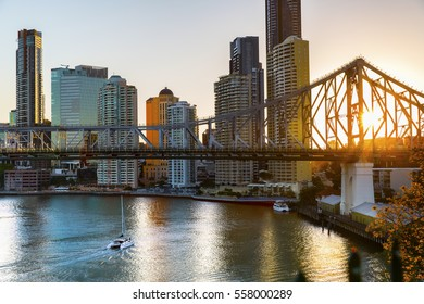 BRISBANE, AUSTRALIA - AUGUST 21 2016: Yacht passing under Brisbane Story Bridge as the sunsets behind the cityscape