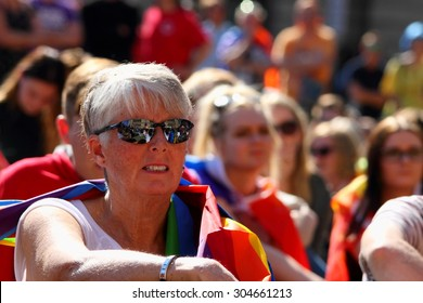 BRISBANE, AUSTRALIA - AUGUST 8 2015: Unidentified rally goer adorned with gay pride flags at Marriage Equality