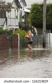 BRISBANE, AUSTRALIA - JANUARY 28 : Unidentified resident taking groceries through flood waters from ex tropical cyclone Oswald on January 28, 2013 in Brisbane, Australia