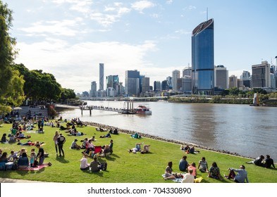 Brisbane, Australia - July 9, 2017: people sitting on the Brisbane River South Bank, watching the Brisbane city skyline.