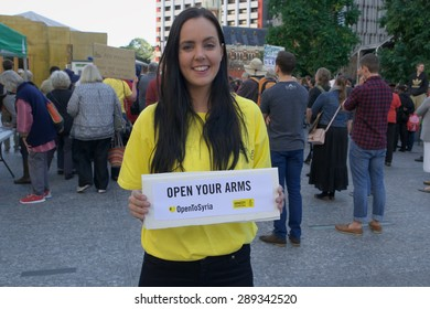 BRISBANE, AUSTRALIA - JUNE 20: Amnesty International volunteer holds sign asking for compassion towards Syrian refugees at World Refugee Day