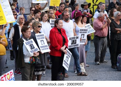 BRISBANE, AUSTRALIA - JUNE 22 : Unidentified protesters holding anti liberal government and reza berati remembrance signs  attending World Refugee Rally June 22, 2014 in Brisbane, Australia